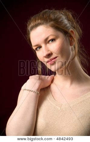 Attractive Female Portrait Modeling In Studio On Dark Red Background