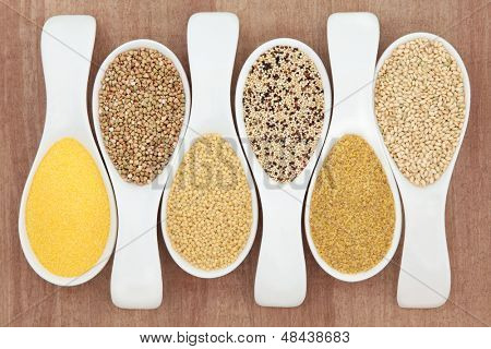 Healthy grain food selection in white porcelain spoons over papyrus background. Polenta, buckwheat, couscous, quinoa, bulghur wheat and sweet rice, left to right.