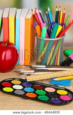 School supplies with apple on wooden table