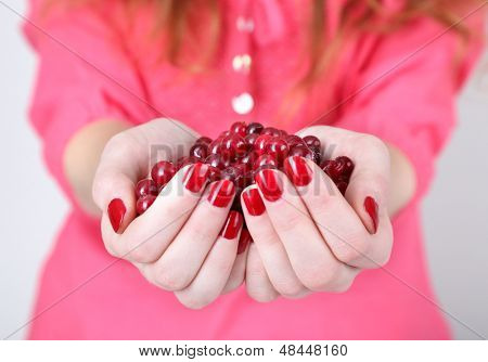 Woman hands holding ripe red cranberries, close up