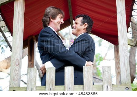 Happy gay couple getting married on the playground of a park.