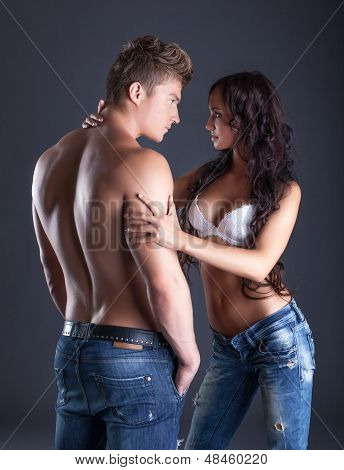 Emotional young couple posing in fashionable jeans
