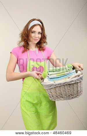 Housewife carrying laundry basket full of clothing on grey background