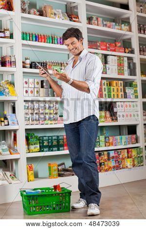 Longitud total del cliente masculino revisando la lista de la compra en el supermercado