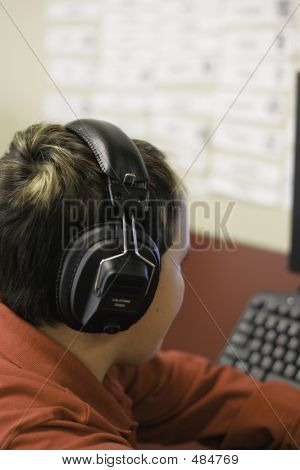 Student At Computer With Headphones