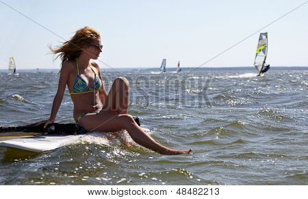 young beautiful woman on windsurfing in water
