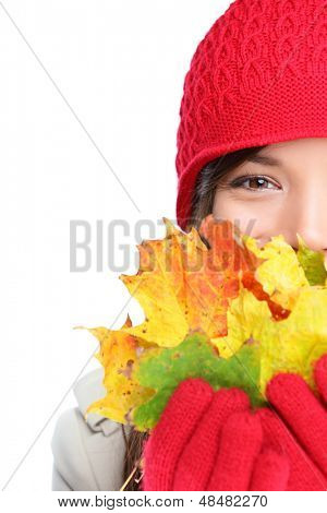 Autumn woman happy with colorful fall leaves isolated on white background in studio. Cheerful girl hiding behind autumn leaves. Portrait close up of multiracial mixed race Asian Caucasian female model
