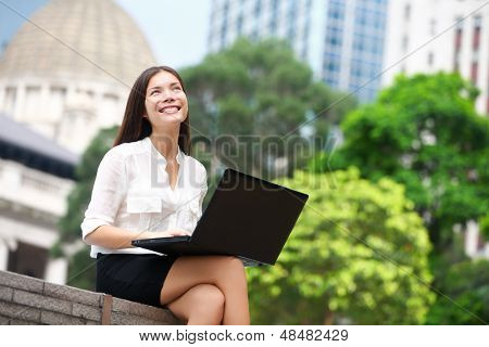 Business woman with computer laptop thinking looking up at copy space in business district, Central, Hong Kong. Young female professional businesswoman sitting relaxing. Asian Chinese Caucasian woman