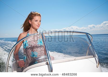 beautiful young woman driving a speedboat and having fun