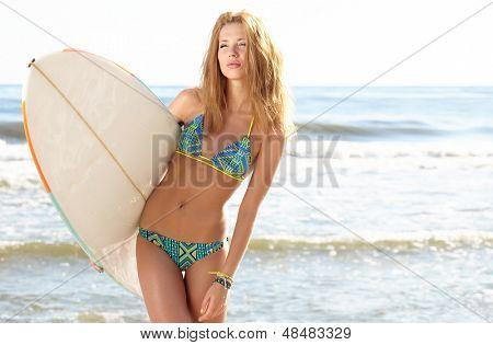 Beautiful sexy young woman surfer girl in bikini with surfboard at a beach