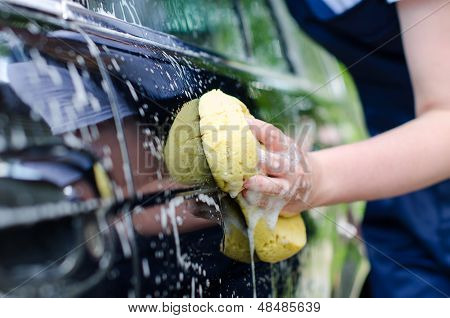 Female Hand With Yellow Sponge Washing Car