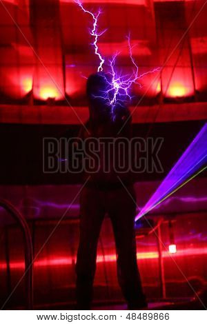 MOSCOW - FEBRUARY 8: Man holds lightning at presentation of attraction Megavolt - master of lightning at VVC, on February 8, 2013 in Moscow, Russia.