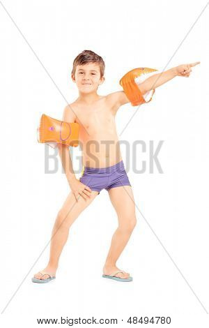 Full length portrait of a boy with swimming arm bands pointing isolated on white background