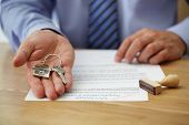 stock photo of real  - Real estate agent handing over house keys with approved mortgage application form - JPG
