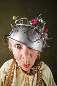 stock photo of crazy hat  - Crazy woman wearing a metal colander for a helmet - JPG