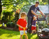 Man And Two Little Sibling Boys Having Fun With Lawn Mower