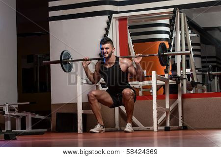 A Physically Fit Men Exercising By Doing Squats