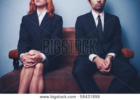 Businessman And Woman Waiting On Sofa In Lobby