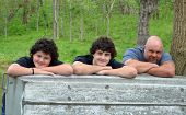 stock photo of loveless  - A father and his two sons resting their heads and arms on a boat in the great outdoors - JPG