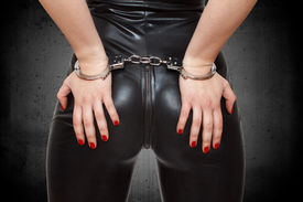 stock photo of handcuff  - Sexy dominatrix hands on ass in handcuffs closeup - JPG