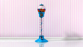 stock photo of gumball machine  - A regular blue vintage gumball dispenser machine made of glass and reflective plastic with chrome trim filled with multicolored gumballs in a retro candy store background with pink striped wallpaper background - JPG