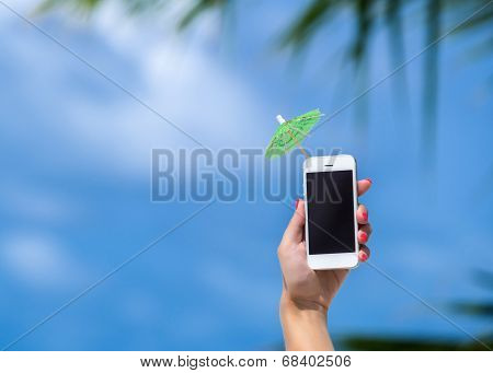 Woman hand showing mobile phone and cocktail umbrella on the sky in the background