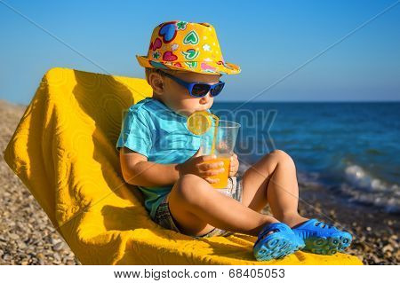 Boy Baby In Sun Glasses And Hat On Beach Drinks Juice