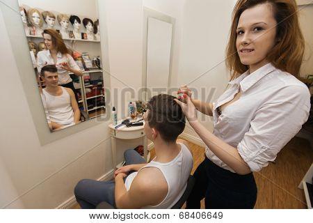 Portrait of female hairstylist cutting male customer's hair in shop