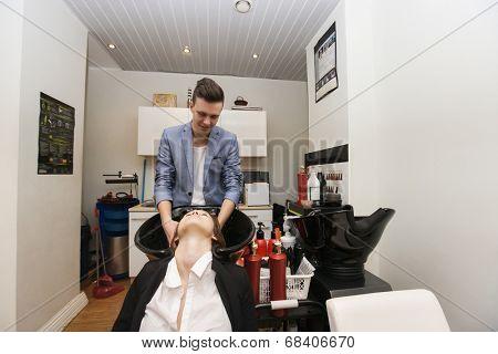 Male hairstylist washing female customer's hair in beauty salon