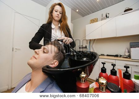 Female hairstylist washing male customer's hair in shop