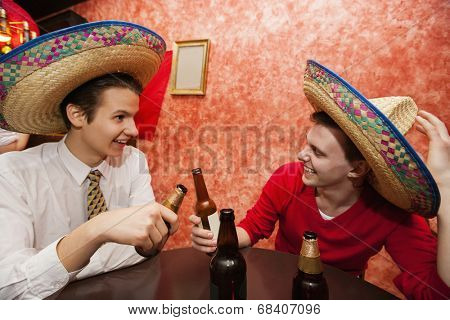 Happy friends wearing Mexican hats toasting at restaurant table
