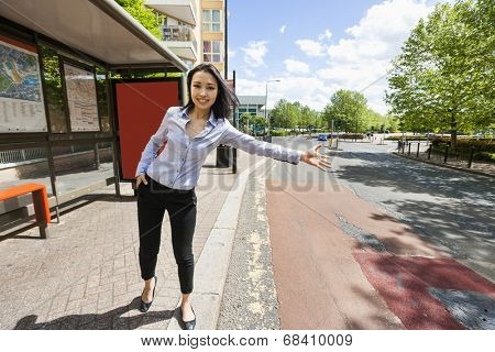 Full length beautiful businesswoman hailing taxi on street