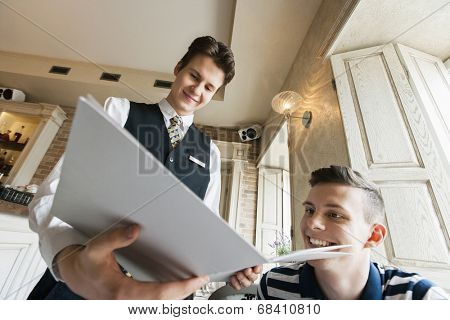 Low angle view of waiter showing menu to male customer in restaurant