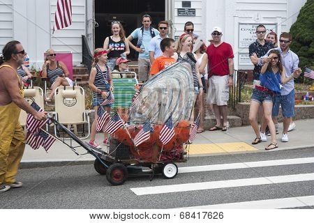 Man pushing giant oyster in the Wellfleet 4th of July Parade in Wellfleet, Massachusetts.