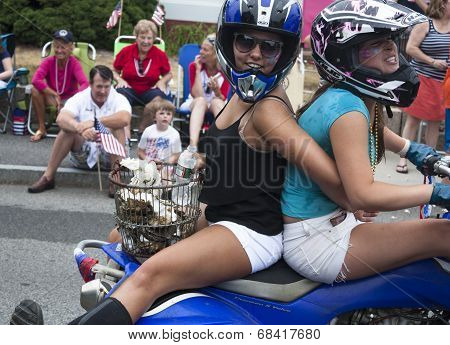 Wellfleet, Massachusetts, USA-July 4, 2014: Two young women riding on a motorcycle in the Wellfleet