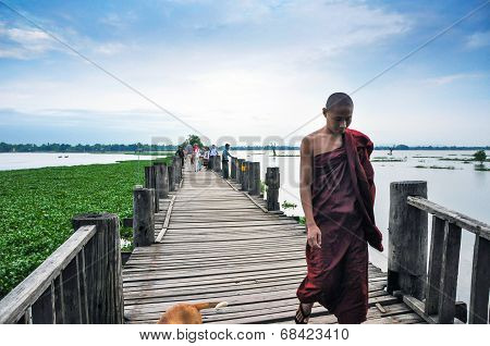 Mandalay, Myanmar - October 9, 2013: Unidentified Young Monk Walking On U Bein Bridge, Myanmar.