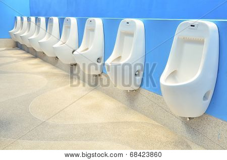 Line Of White Urinals With Colorful Blue Wall In Public Toilet