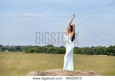 Young beautiful girl in the hayloft in the village