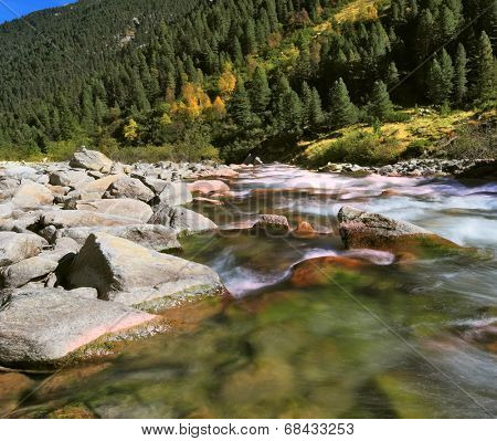 Pastoral in the Alpine mountain valley in Austria. Rapid mountain stream. Cascades of cold water at the source of the Krimml waterfalls