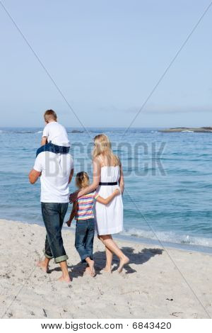 Familia alegre caminar sobre la arena
