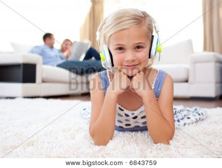 Smiling Little Girl Listening Music Lying On The Floor