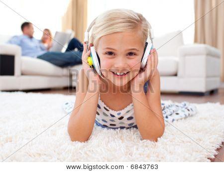 Happy Little Girl Listening Music Lying On The Floor