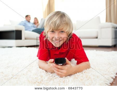 Smiling Boy Watching Tv Lying On The Floor