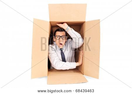 Young businessman trapped in a box isolated on white background