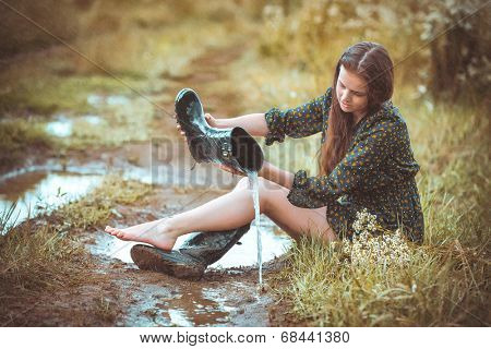 girl sitting on rural road in time a rain