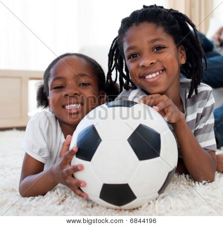 Little Girl And Her Brother Holding Soccer Ball