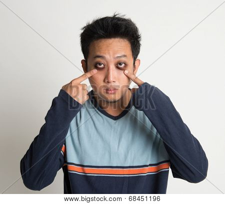 Asian man insomnia, with big eyes bag, on plain background