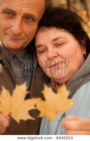Serious middleaged man and woman hold maple leaves
