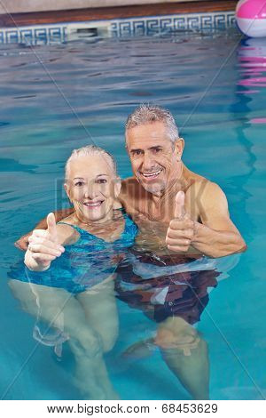 Happy senior couple bathing in swimming pool holding their thumbs up