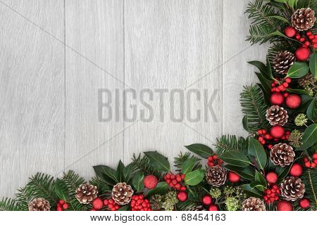 Christmas background border decoration with red baubles, holly, ivy, fir leaf sprigs and pine cones.